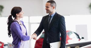 Smiling salesman shaking the hand of a woman in a car shop © wavebreakmedia/Shutterstock.com