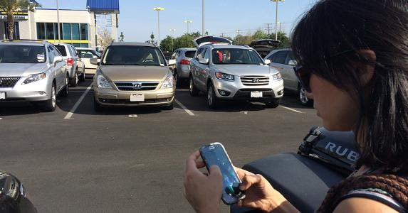 Woman in car lot checking smartphone
