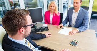 Couple with car salesman in office © Kzenon/Shutterstock.com
