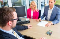 Couple with car salesman in office
