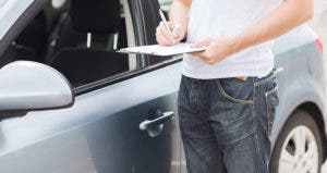 Man standing next to a car, signing documents © Syda Productions/Shutterstock.com