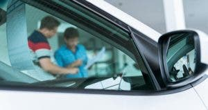 Looking through car window at car salesman and buyer © Greentellect Studio/Shutterstock.com