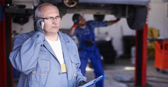Car mechanic calling customer © gpointstudio/Shutterstock.com