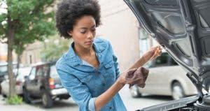 Woman checking car's oil levels | Jose Luis Pelaez Inc/Getty Images