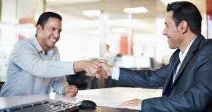 Businessmen shaking hands in an office | iStock.com/kupicoo