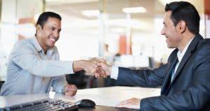 Businessmen shaking hands in an office | iStock.com/kupicoo
