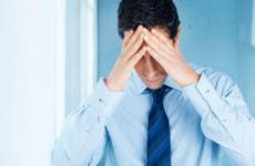 Businessman holding his head in regret © iStock