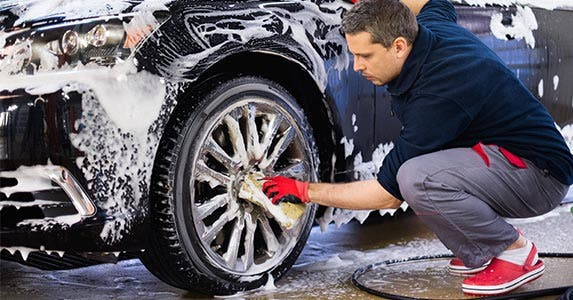 Man washing his car, detailing the tire rims