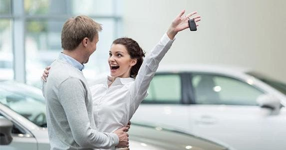 Couple cheering after buying car | Lucky Images/Shutterstock.com