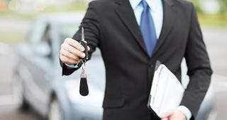 Car salesman holding keys © Syda Productions/Shutterstock.com