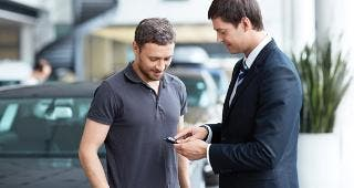 Young man with car salesman © LuckyImages/Shutterstock.com