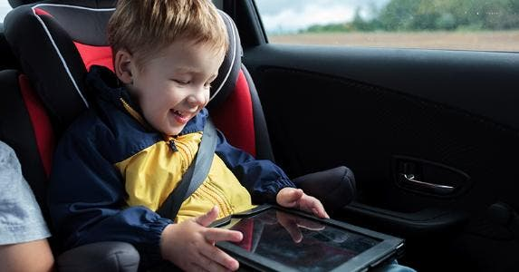 Smiling little boy sitted on back seat of the vehicle, playing with tablet