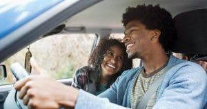 Smiling young couple in car | Hero Images/Getty Images