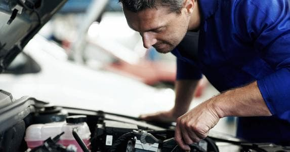 Mechanic working under hood of car | iStock.com/kupicoo