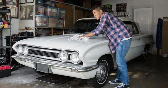 Young man washing his classic car   Hero Images/Getty Images