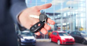 Man holding car keys in front of dealership © kurhan/Shutterstock.com