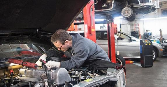 Car mechanic working on engine | Reza Estakhrian/Getty Images
