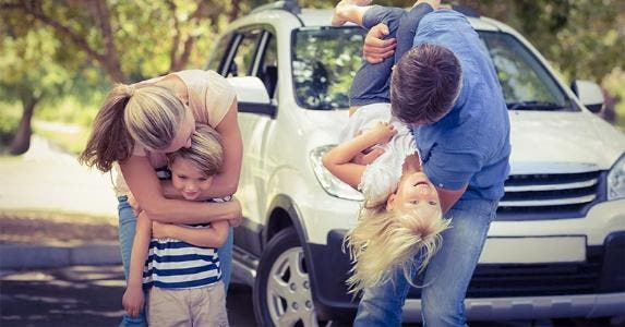 Parents playing and hugging children, family vehicle on the background © wavebreakmedia/Shutterstock.com