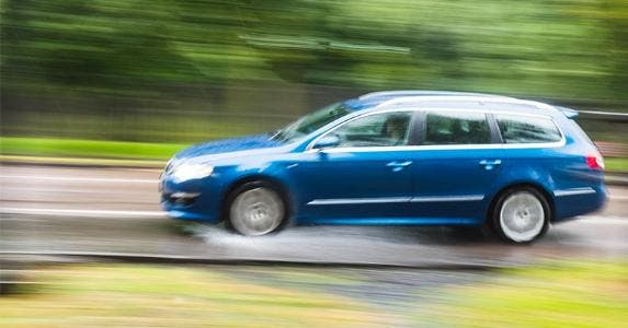 Car driving fast in the rain | Joseph O. Holmes/Getty Images