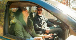 Couple driving in the woods, laughing in their car | Aaron Greene/Blend Images/Getty Images