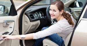 Smiling young woman closing car door © Viktor Cap - Fotolia.com