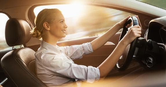 Woman driving her car at sunset © iStock