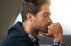 Pensive man in plaid shirt and blue jacket © iStock