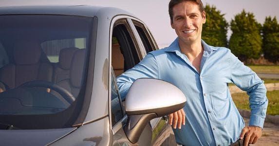 Smiling man standing next to grey vehicle | iStock.com/stockvisual