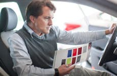 Man holding sales packet inspecting car in front seat | Zero Creatives/Getty Images