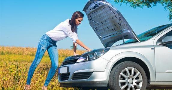 Woman checking under car's hood © TijanaM/Shutterstock.com