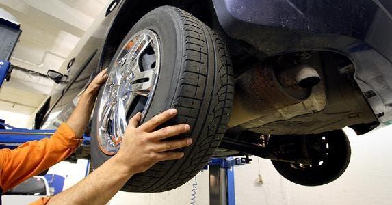 Mechanic installing new tire on vehicle