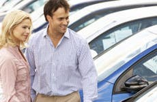 Couple shopping for a new car on a dealership lot © Monkey Business Images/Shutterstock.com