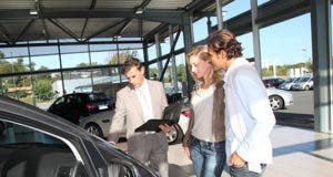 Couple with car salesman in showroom © goodluz - Fotolia.com