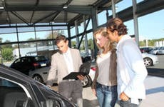 Couple with car salesman in showroom © goodluz - Fotolia.com