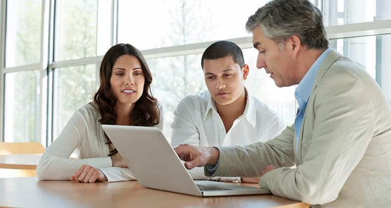 Adviser showing laptop's screen to client couple | iStock.com