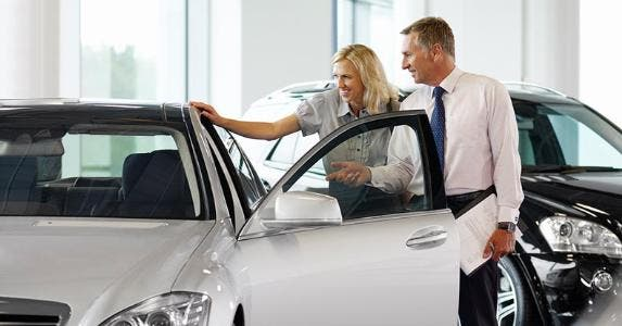 Woman with salesman, checking out car in showroom | Adam Gault/Getty Images