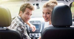 Couple seated in front seat of car, looking back © Jack Frog/Shutterstock.com