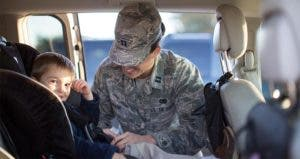 Mother wearing Air Force uniform putting child in car seat | Sean Murphy/Getty Images