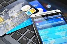 Mobile banking app and credit cards on keyboard © Oleksiy Mark/Shutterstock.com