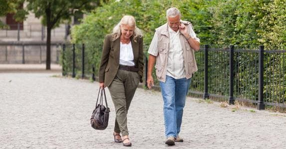 Couple walking together in city park © iStock