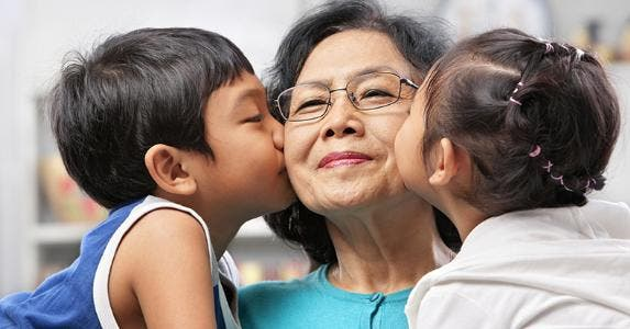 Grandmother getting kissed by grandchildren © iStock