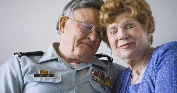 Senior military veteran resting head against wife | rubberball/Getty Images