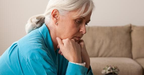 Sad senior woman sitting on couch © Tetra Images/Corbis