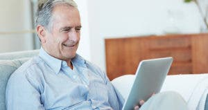 Senior man smiling while using his tablet © iStock