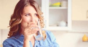 Woman sipping a glass of water © iStock.com/elenaleonova