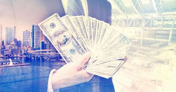Business man holding wealth of money © iStock