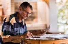 Older man doing paperwork | skynesher/Getty Images