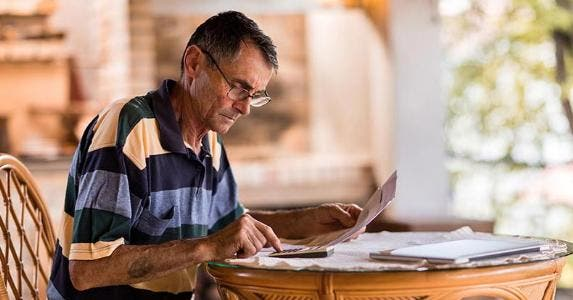 Older man doing paperwork | skynesher/Getty Images
