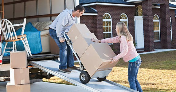 Man and woman loading boxes into a truck