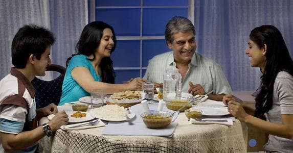 Family eating dinner at table, together © India Picture/Shutterstock.com